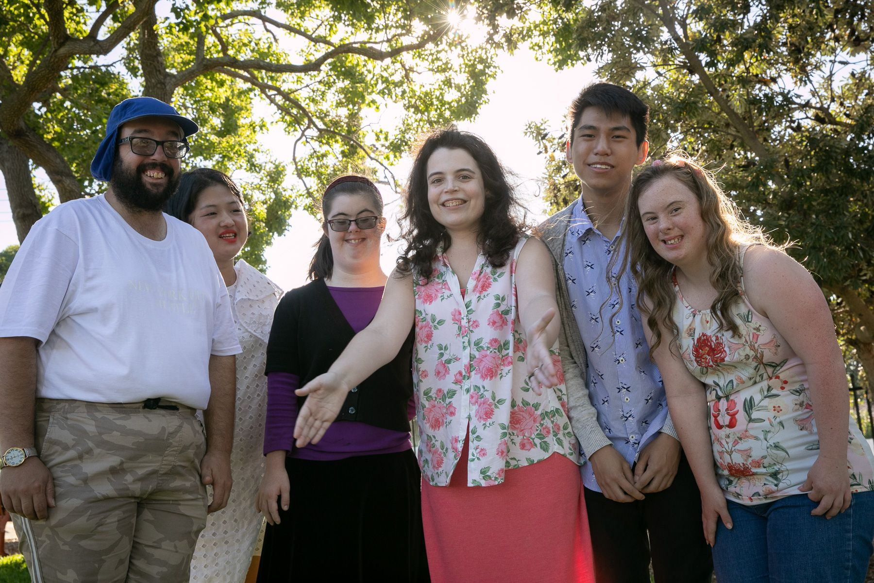 A group of young people with intellectual disability stand in the sunshine